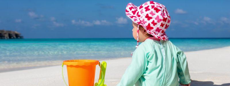 Baby sitzt am Strand und spielt mit seinen bunten Spielsachen im Sand