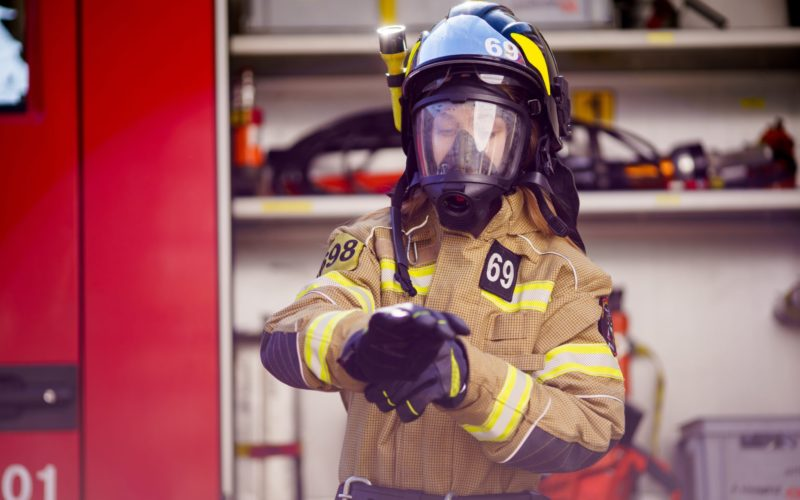 Photo of woman firefighter in helmet and mask standing near fire truck at fire station