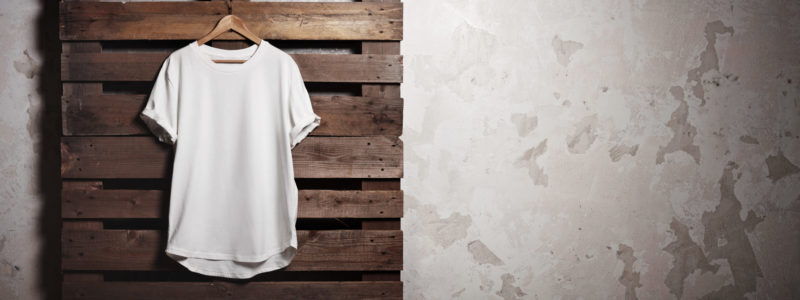 Photo of white tshirt  hanging in front of concrete wall. Wide, soft shadows.